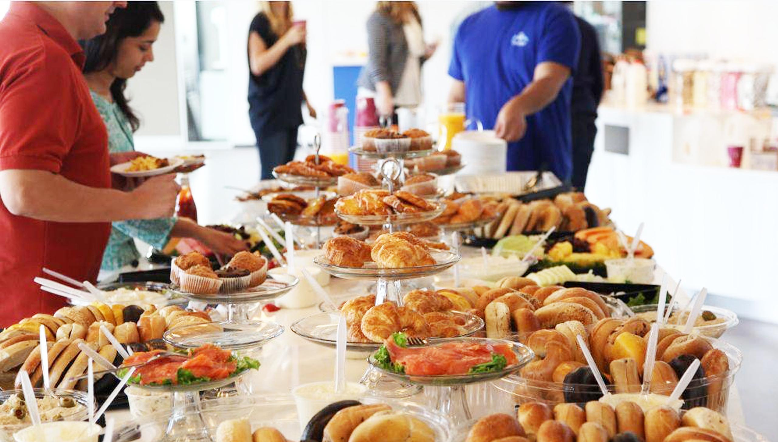 Een tafel met een buffet voor de lunch. Verschillende soorten brood, croissantjes en muffins